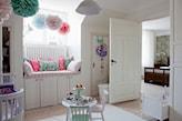 biały dywan, okrągły stolik dziecięcy, kolorowe kule wiszące w pokoju dziecka