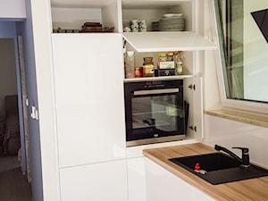 Biała kuchnia z połączeniem drewna
