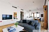 salon w stylu skandynawskim, szara sofa, drewniany stół, białe ściany
