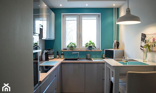 kuchnia z niebieską ścianą i białymi meblami