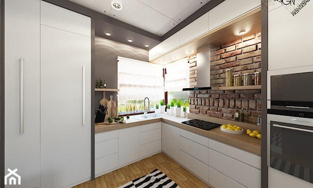 białe meble kuchenne z drewnianymi blatami i z ceglaną ścianą