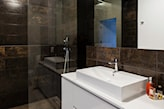 kabina prysznicowa walk in, białe meble łazienkowe z połyskiem, czarne płytki łazienkowe