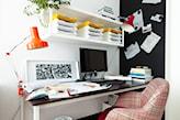 czarna tablica ścienna, fotel w różową kratkę, pomarańczowa lampa biurowa