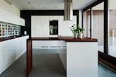 białe meble kuchenne z drewnianym blatem, czarna ściana, okap w kształcie walca