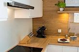 kuchnia w stylu skandynawskim, białe meble z drewnianym blatem, świeże zioła w doniczce