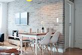 ceglana ściana, drewniana podłoga, białe krzesła, drewniany stół z białymi nogami