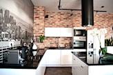 cegła naturalna, białe meble z połyskiem z czarnym blatem, fototapeta w kuchni z panoramą miasta