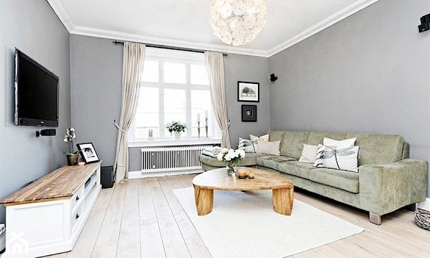 szare ściany, podłoga z jasnego drewna, kremowy dywan, szare zasłony, trójkątny stolik