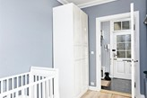 biała szafa, białe łóżeczko dziecięce, drewniana podłoga, siwe ściany