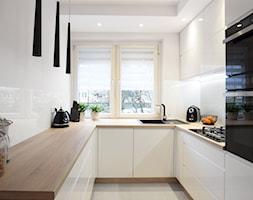 Kuchnia w bloku - Układ U - Średnia otwarta wąska biała kuchnia w kształcie litery u z oknem, styl nowoczesny - zdjęcie od FORMA-MEBLE.PL