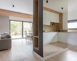 Projekt domu w okolicach Poznania ok. 120 m2 - Duża otwarta biała szara kuchnia w kształcie litery g z oknem, styl nowoczesny - zdjęcie od Architektownia
