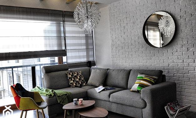 salon w stylu industrialnym, szara cegła, okrągłe lustro ścienne, szary narożnik, drewniane stoliki