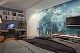 sypialnia z tapetą z mapą świata w niebieskich barwach, białe drzwi, szara narzuta