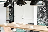 drewniany stół. druciane krzesła, białe rysunki na ścianie pomalowanej farbą tablicową