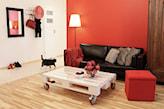 czarna sofa ze skóry, czerwona ściana, czerwona pufa, czerwony koc