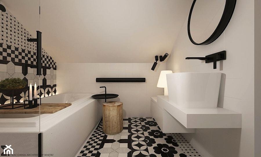 płytki w biało-czarne wzory, stołek z pieńka, czarne świeczniki w łazience