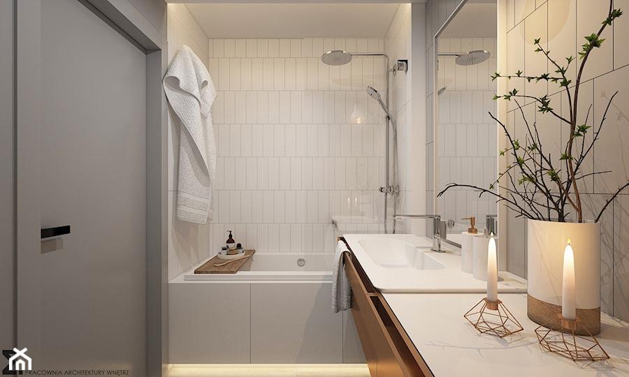 białe kafelki w łazience, złote świeczniki, biały wazon