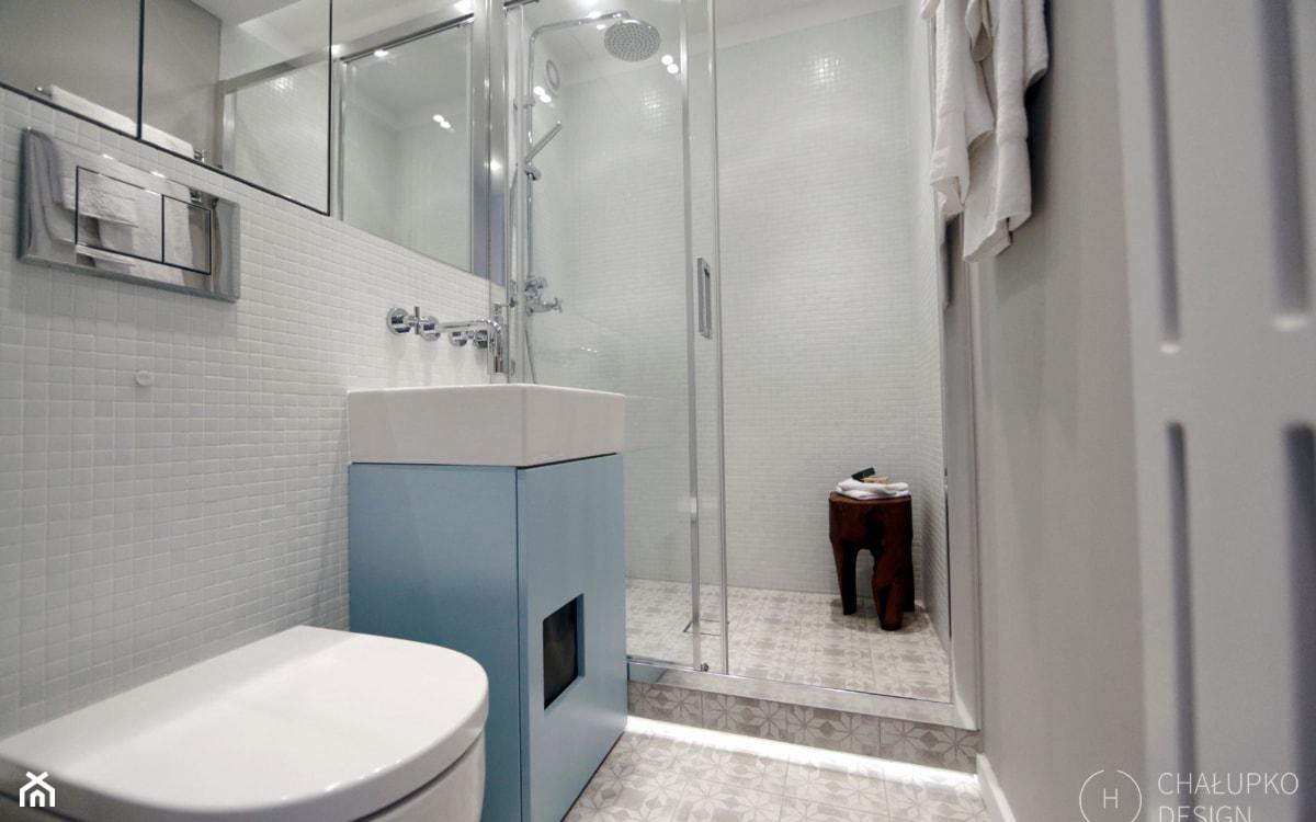 błękitna szafka łazienkowa, białe kafelki, kabina prysznicowa walk-in
