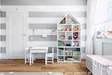 ściana w biało-szare pasy, biały regał domek, drewniana podłoga, biały wiklinowy kosz
