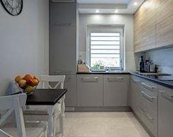 Kuchnia w szarości i drewnie. - Mała zamknięta biała kuchnia w kształcie litery l, styl nowoczesny - zdjęcie od Carolineart