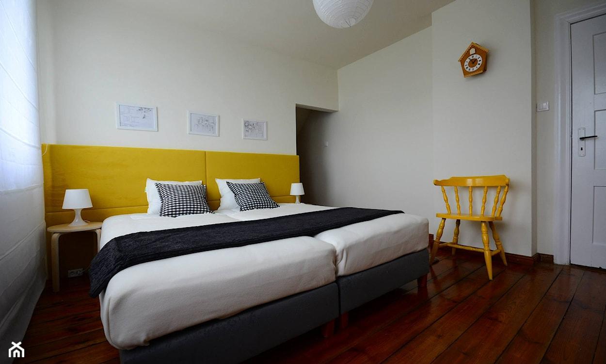 żółty zagłówek, podłoga z ciemnego drewna, żółte krzesło, grafitowa narzuta na łóżko