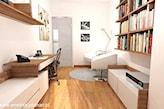 podłoga z jasnego drewna, biały fotel, okrągły dywan, biała lampa podłogowa, drewniany regał z książkami