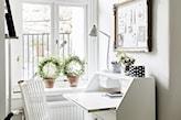 białe biurko, białe krzesło, biała lampa biurowa, tablica na notatki ze złotą ramą