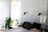 szare ombre na ścianie, lampa-żarówka, czarne poduszki