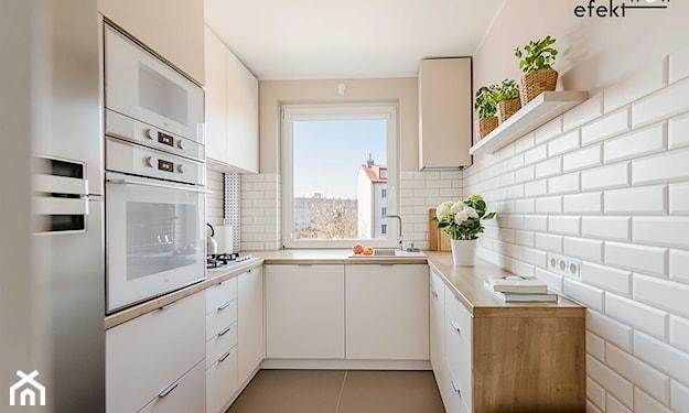 białe meble w kuchni i okap z ozdobą