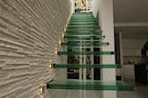 ściana z kamienia ozdobnego i schody z zielonego szkła