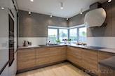 drewniane szafki kuchenne, szary blat kuchenny, biały okap o owalnym kształcie