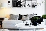 biało-czarny salon, biała sofa, poduszki w paski, lampa podłogowa z białym abażurem, dekoracja ścienna z biało-czarnych grafik