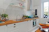drewniany blat kuchenny, białe kafelki do kuchni, białe półki w kuchni