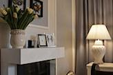 biała lampa stołowa, biały kominek. żółte tulipany, zdęcia