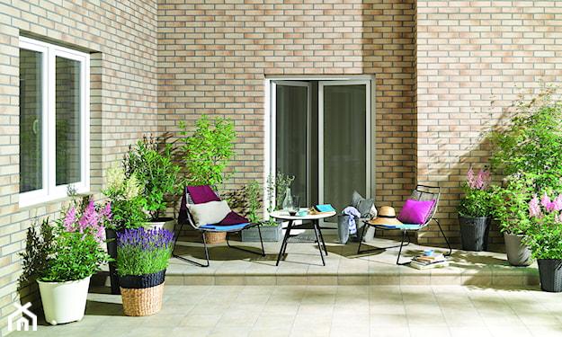 elewacja z beżowej cegły, metalowe meble ogrodowe, donice z plecionki