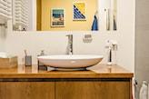 drewniane meble z połyskiem, lustro bez ramy, białe płytki łazienkowe
