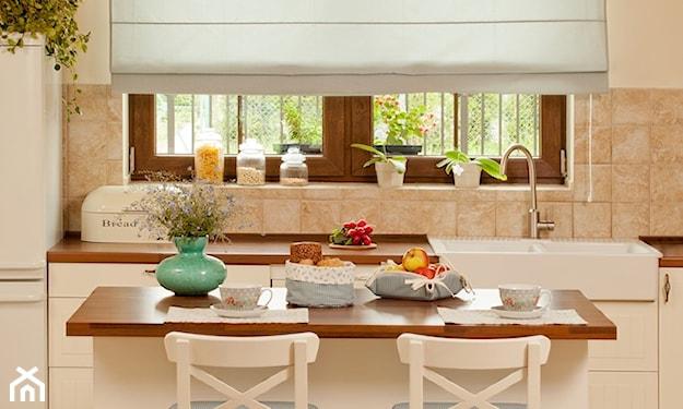 białe meble kuchenne z drewnianym blatem, białe hokery z błękitnymi nakładkami, błękitna roleta rzymska