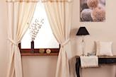 kremowe zasłony, lampa stołowa z czarnym abażurem, zdjęcie z kwiatami