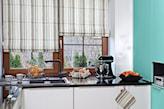 kuchnia z białymi szafkami i czarnymi blatami z połyskiem