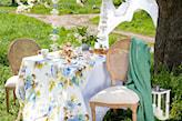 biały obrus w niebieskie kwiaty, zielona narzuta, biała latarenka, zielony ogród