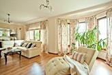 drewniana podłoga, beżowa sofa, beżowa leżanka, cienkie zasłony w kolorowe kwiaty