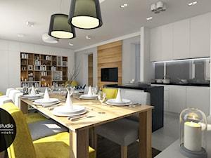 Nowoczesna otwarta na salon kuchnia w minimalistycznym charakterze z dodatkiem