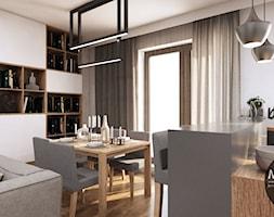 Ciepła jadalnia otwarta na kuchnię i salon - zdjęcie od MONOstudio