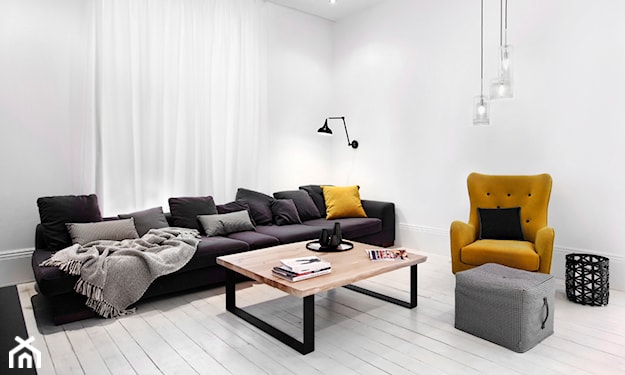 żółty fotel, czarna sofa, białe ściany