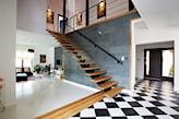 drewniane schody bez balustrady, betonowe płytki na ścianie, biało-czarne płytki