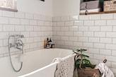 łazienka z wanną i cegiełką na ścianie