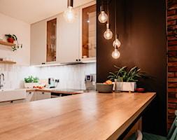 Stół między aneksem kuchennym a salonem z oprawami na kablach - zdjęcie od Wnętrzowe Love - Homebook