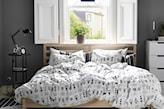 drewniana rama łóżka, biała pościel we wzory, biała komoda, grafitowe ściany, czarna lampka nocna
