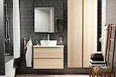 łazienka z ciemnymi płytkami z drewnianymi meblami