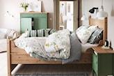 zielona szafka nocna, drewniana rama łóżka, biała pościel w kwiaty, biała lampa wisząca